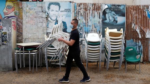 Un camarero recoge un bar en Sevilla, España.