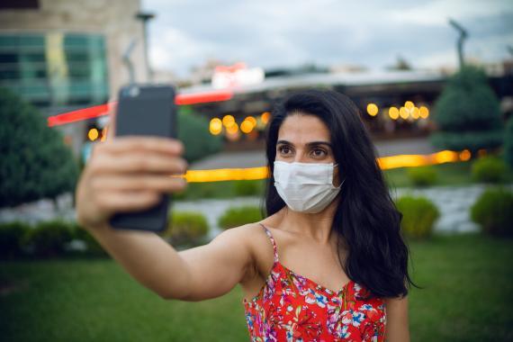 Una chica se hace un selfie con mascarilla.