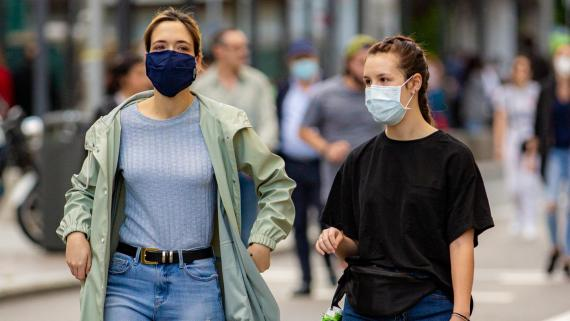 Chicas con mascarillas andando por la calle.