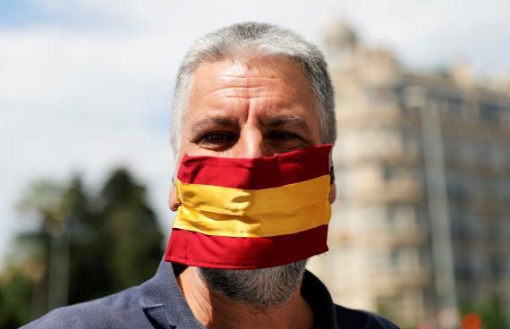 Un hombre con una mascarilla con la bandera de España.