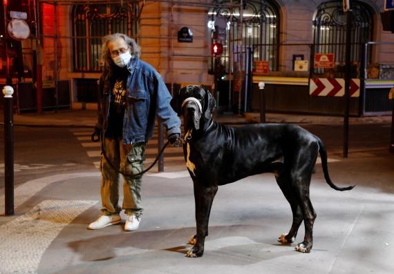Hombre paseando a su perro por la noche