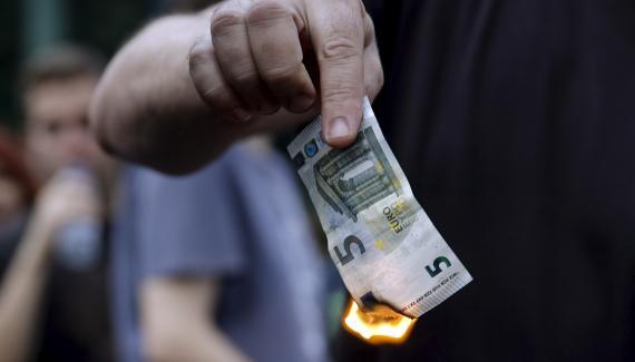 Un manifestante quema un billete de 5 euros en una protesta contra las medidas de austeridad en Grecia