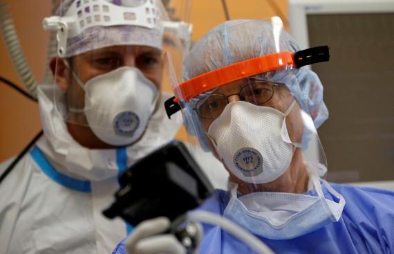 Médicos miden las constantes vitales de un paciente con COVID-19.