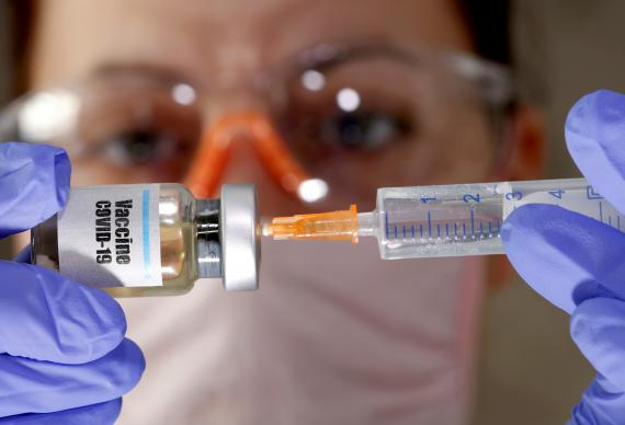 Mujer con un bote con la vacuna del covid 19