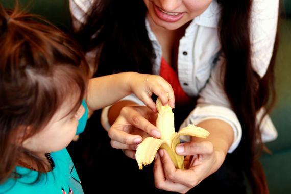 mujer dando fruta a un niño, plátano.