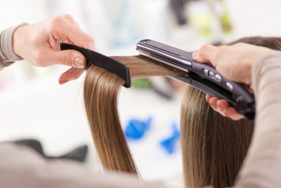Una mujer se plancha el cabello.