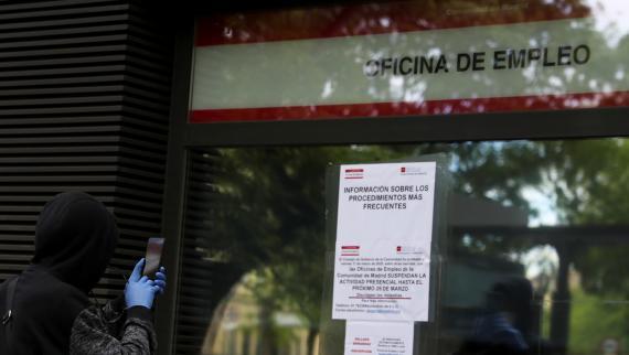 Una persona fotografía los avisos ante el coronavirus en una oficina de empleo de Madrid