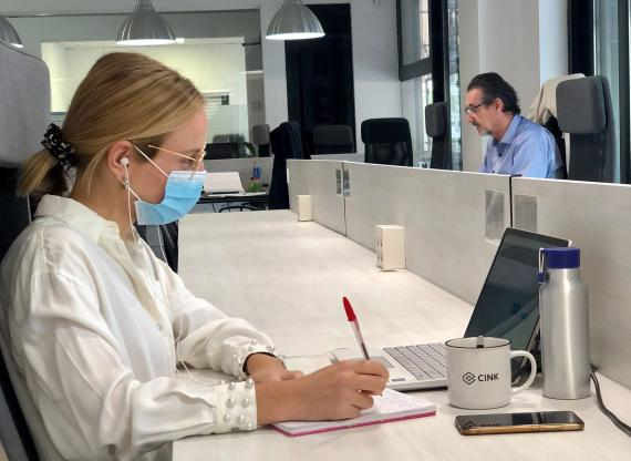 Una persona trabaja con mascarilla en un espacio de Cink Coworking en Madrid