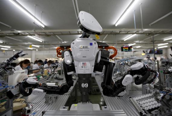 Un robot trabaja junto a empleados de la empresa Glory Ltd en Kazo, al norte de Tokio, en Japón.