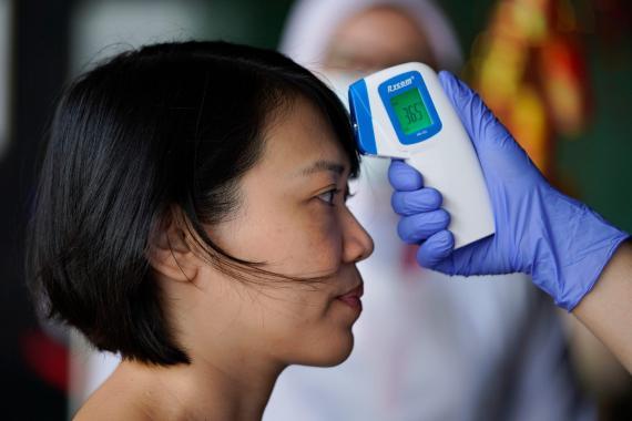 Una mujer se toma la temperatura corporal en medio de un brote de coronavirus.