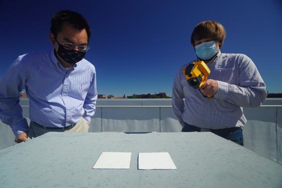 Xiulin Ruan (izquierda) y Joseph Peoples usan una cámara infrarroja para comparar el rendimiento de enfriamiento de las muestras de pintura blanca en un tejado.