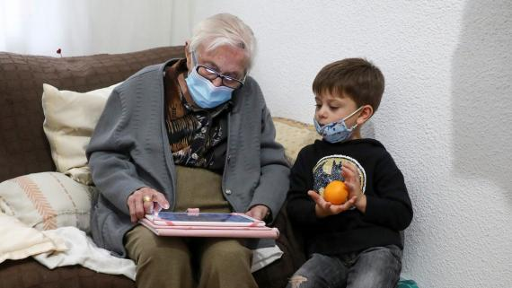 Una abuela y su nieto miran una tablet durante la pandemia de coronavirus
