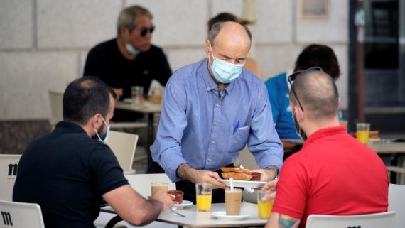 Un camarero sirve a 2 clientes con mascarilla en una terraza de Madrid