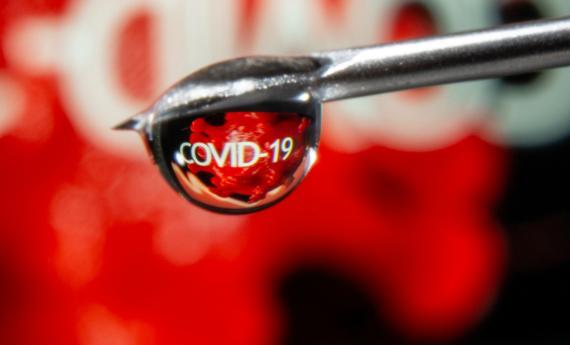 Una gota refleja la palabra COVID-19 en una jeringuilla