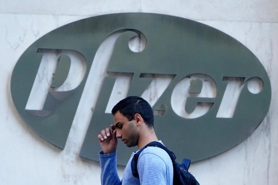 Un hombre camina delante de la sede de Pfizer