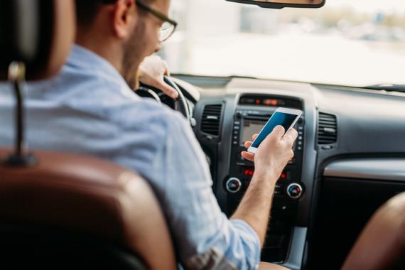 Hombre conduciendo con el móvil.
