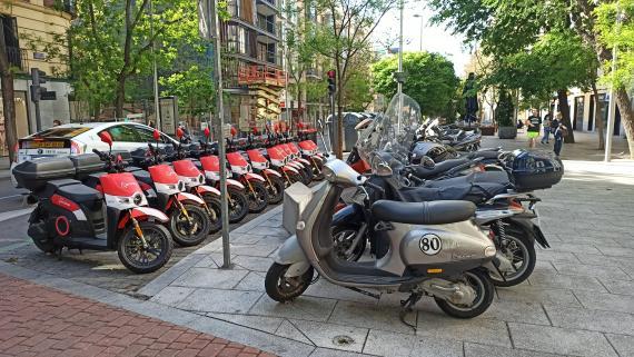 Motos eléctricas compartidas de Acciona ocupando toda una zona de aparcamiento en la calle Fuencarral, en Madrid.
