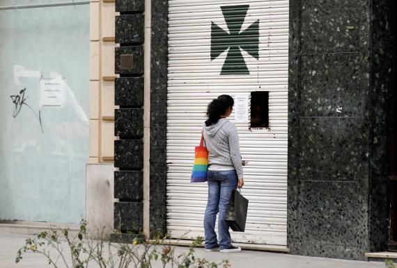 Una mujer delante de una farmacia