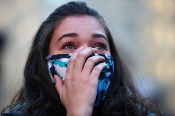 Mujer con mascarilla llorando.
