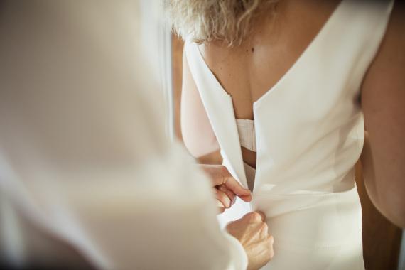 mujer subiéndose cremallera vestido