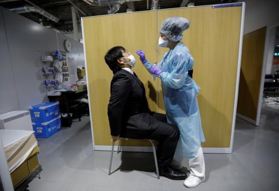 Un viajeo sometiéndose a una prueba en el Centro de PCR del Aeropuerto Internacional de Narita, en Japón.