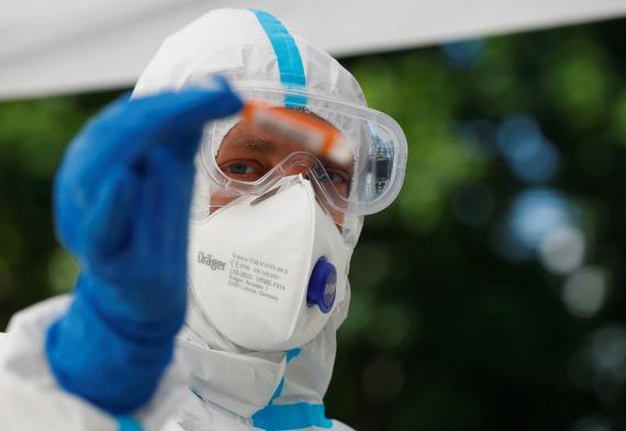 Sanitario con traje de protección con un test rápido de COVID-19.