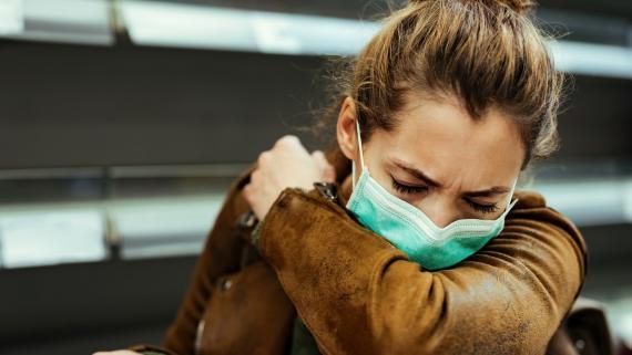 Chica tosiendo con una mascarilla puesta.