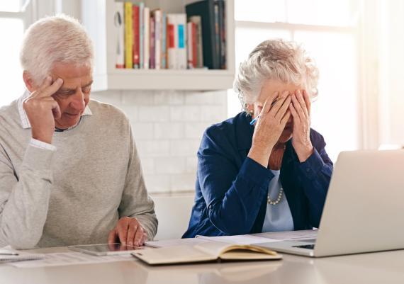 Dos personas mayores se lamentan delante de un ordenador y unos cuantos papeles.