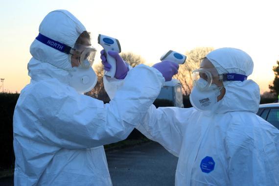 Dos sanitarios se controlan la temperatura corporal en medio de la pandemia del coronavirus