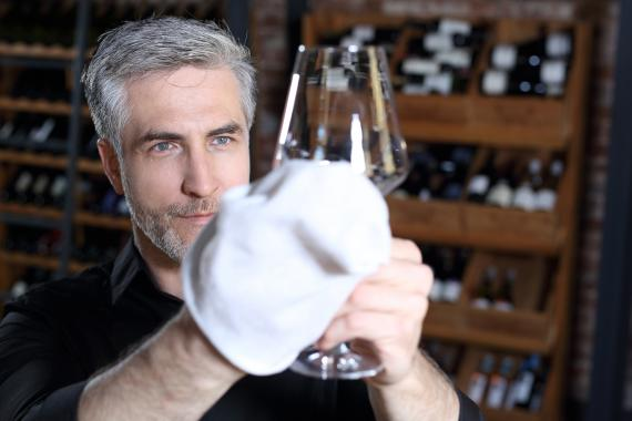 Hombre limpiando una copa de vino.