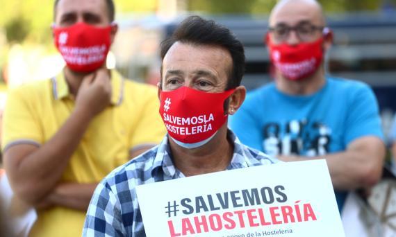 Un hombre con mascarilla muestra una pancarta en apoyo al sector hostelero en Madrid