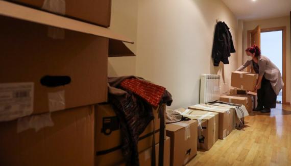 Una mujer con mascarilla hace la mudanza a su piso de alquiler en Fuenlabrada (Madrid)