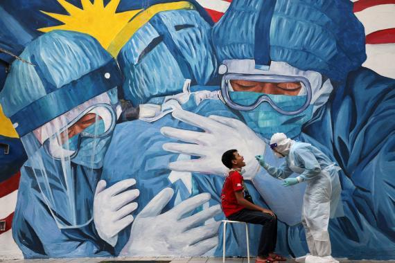 Un mural sobre la lucha de los médicos contra el coronavirus frente a una prueba PCR