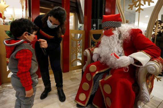 Un Papa Noel se saca fotos con los niños en un centro comercial