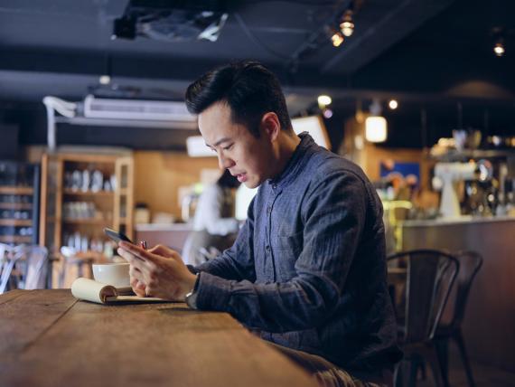 Una persona consulta el móvil y toma apuntes en un bar