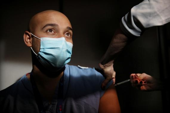 Un profesional sanitario recibe una de las primeras vacunas de Pfizer y BioNTech