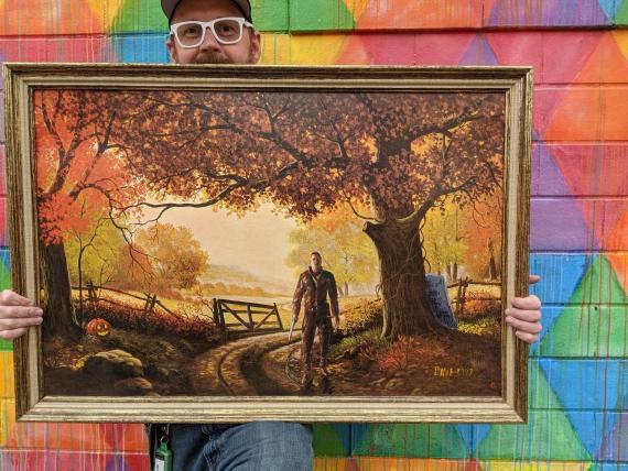 David Sherrill posa con un cuadro de Michael Myers, el antagonista de la saga 'Halloween', pintado sobre un sereno fondo otoñal.