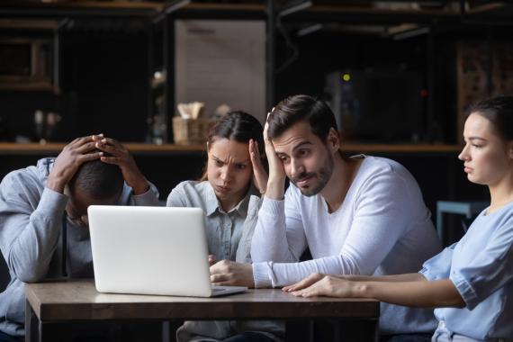 Varias personas miran un ordenador con cara de decepción.