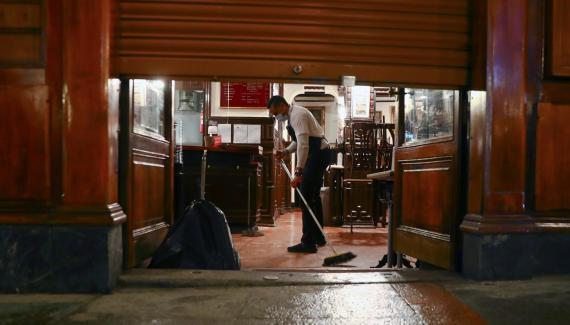 Un camarero friega el suelo de un bar de Madrid antes del toque de queda