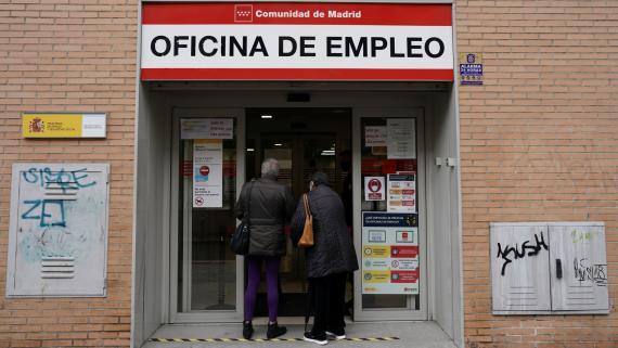 Dos desempleados con mascarilla hacen cola en una oficina de empleo en Madrid