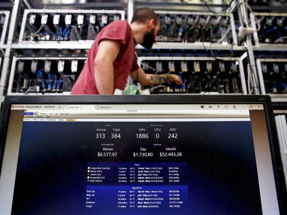 A bitcoin-mining computer and a screen showing bitcoin exchange rates at Bitminer Factory in Florence, Italy.