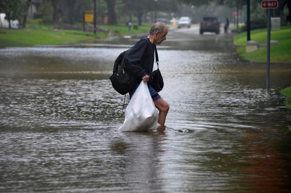 Un hombre carga con sus pertenencias durante las inundaciones de 2017 en Texas (Estados Unidos) provocadas por el huracán Harvey.