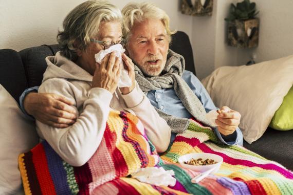 Un hombre y una mujer se protegen del frío con una manta en un sofá.