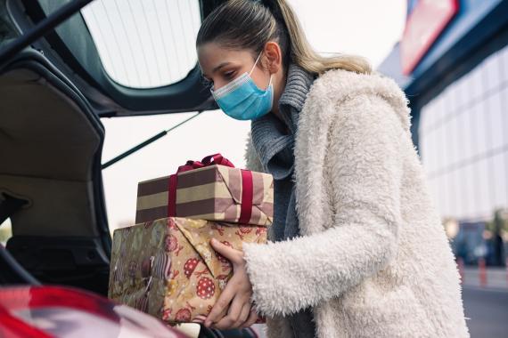 Mujer guardando regalos en el maletero del coche.