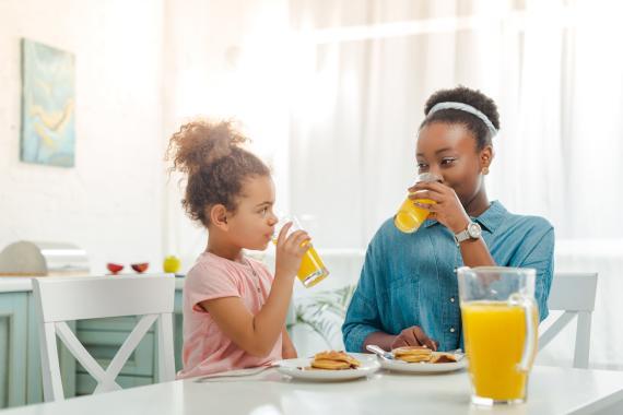 Mujer e hija bebiendo zumo