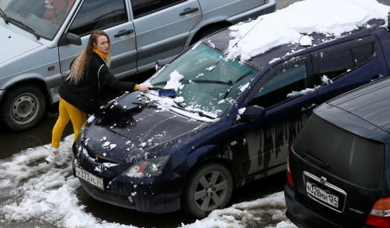 Mujer limpiando la nieve de su coche
