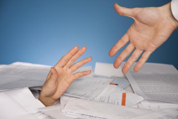 Una persona trata de sacar a otra de una montaña de papeles.