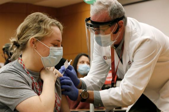 La empleada del estado de Ohio, Estados Unidos, Lauren Chisholm, izquierda, recibe una vacuna Pfizer-BioNTech COVID-19 por Robert Weber.
