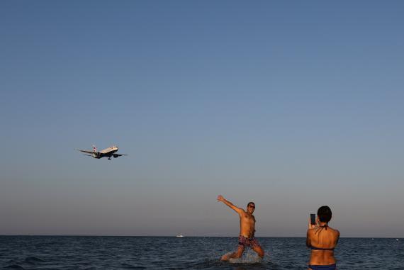 Turistas en la playa se hacen fotos con un avión que va a aterrizar en el Aeropuerto Internacional de Lárnaca.