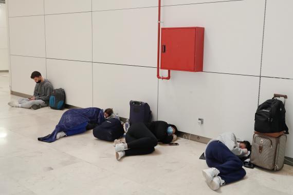 Varias personas descansan en el Aeropuerto de Barajas (Reuters)